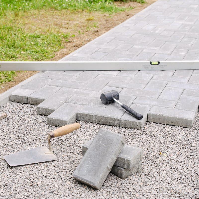 Bloques de la piedra con la herramienta para pavimentar el fondo de la fijación Concepto del arquitecto de Hausework fotos de archivo