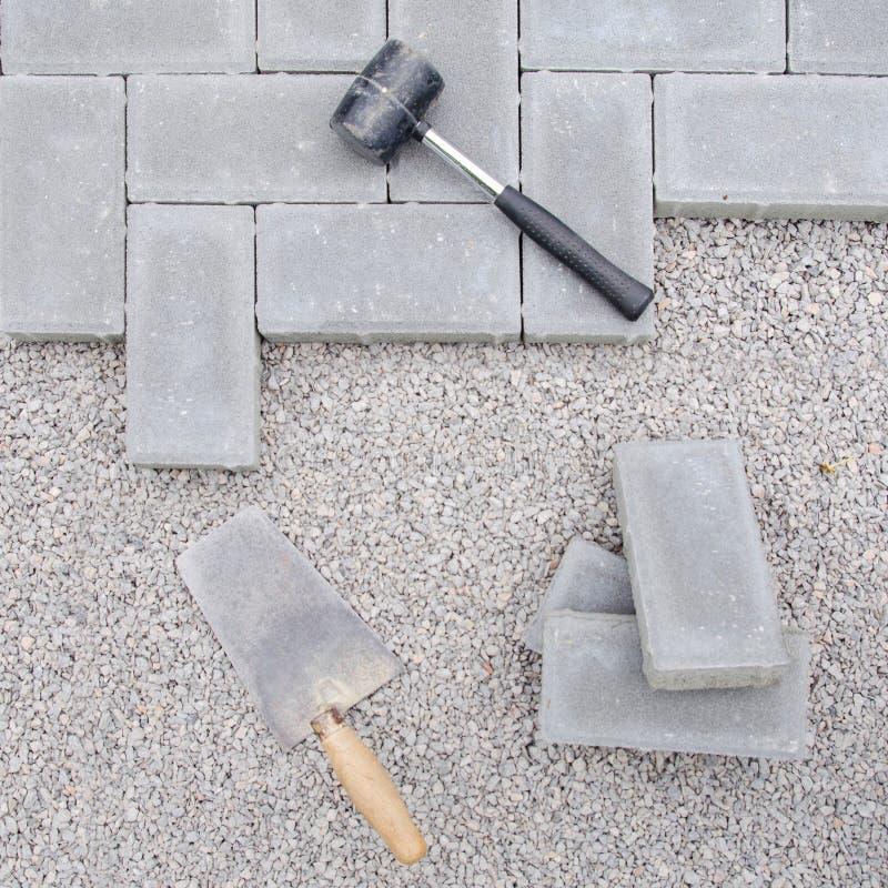 Bloques de la piedra con la herramienta para pavimentar el fondo de la fijación Concepto del arquitecto de Hausework foto de archivo
