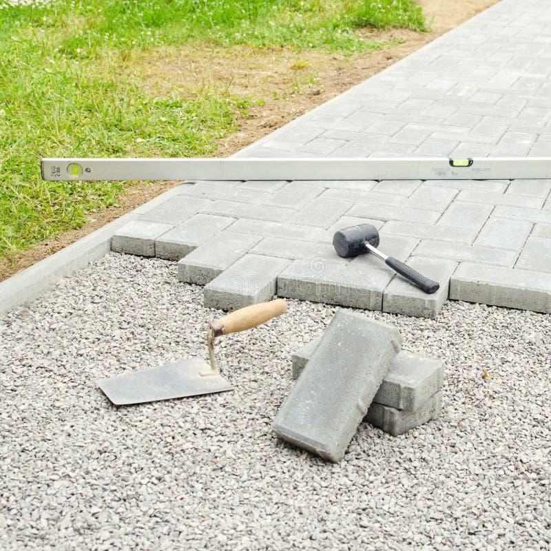 Bloques de la piedra con la herramienta para pavimentar el fondo de la fijación Concepto del arquitecto de Hausework fotografía de archivo libre de regalías