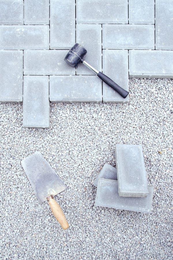 Bloques de la piedra para pavimentar el fondo de la fijación con el martillo y la paleta fotografía de archivo