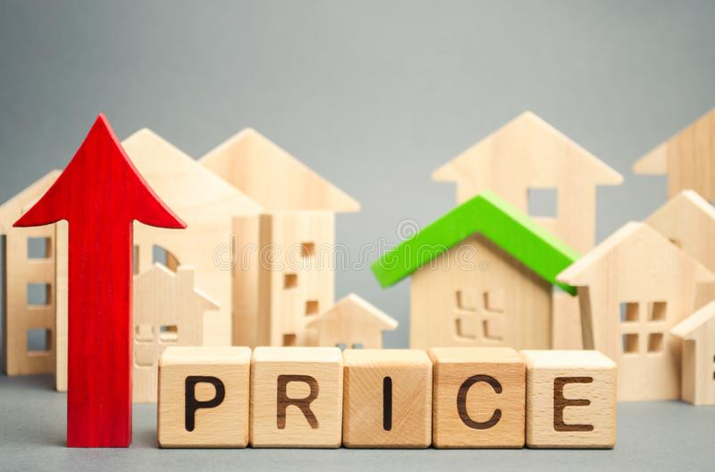 Bloques de madera con el precio de la palabra, encima de la flecha y de casas de madera El aumento en precios de vivienda Alquile imagen de archivo libre de regalías