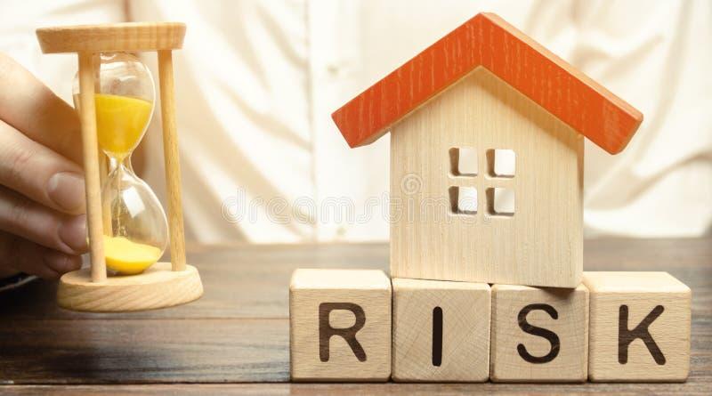 Bloques de madera con el riesgo de la palabra, la casa y el reloj El concepto de impago de los tipos de inter?s en hipotecas Casa fotos de archivo libres de regalías