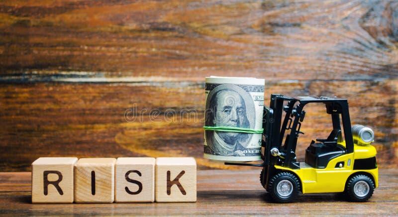 Bloques de madera con el riesgo de la palabra, el dinero y una carretilla elevadora Concepto financiero y comercial del riesgo In fotografía de archivo