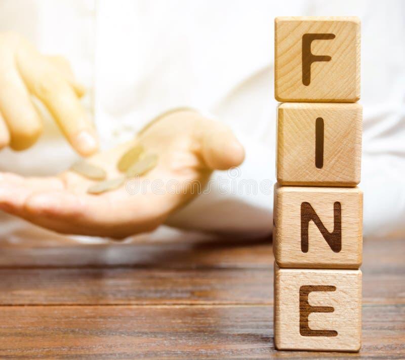 Bloques de madera con la multa de la palabra y un hombre que calcula el tama?o de la multa Pena monetaria impuesta bajo la forma  fotos de archivo
