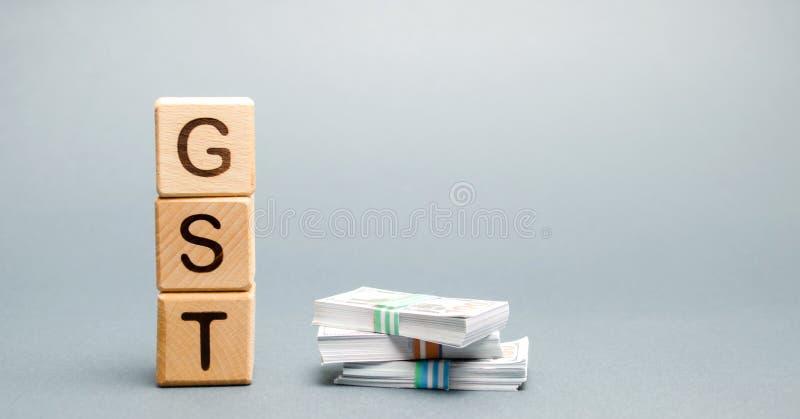 Bloques de madera con las mercancías de la palabra GST y el impuesto y el dinero de servicios Impuesto, que se impone ante la ven imagenes de archivo