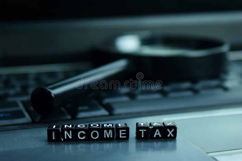 Bloques de madera del texto del impuesto sobre la renta en fondo del ordenador portátil Concepto del negocio y de la tecnología imágenes de archivo libres de regalías
