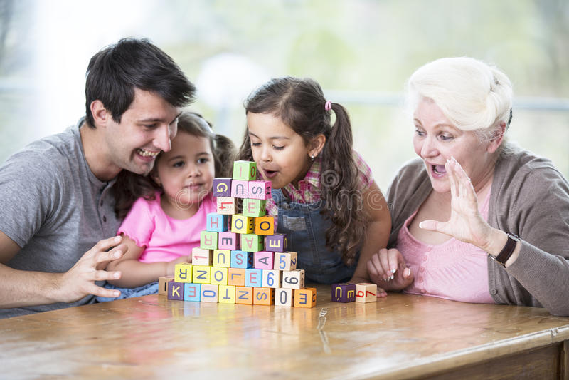 Bloques del alfabeto de la muchacha que soplan linda mientras que familia que lo mira en casa fotografía de archivo