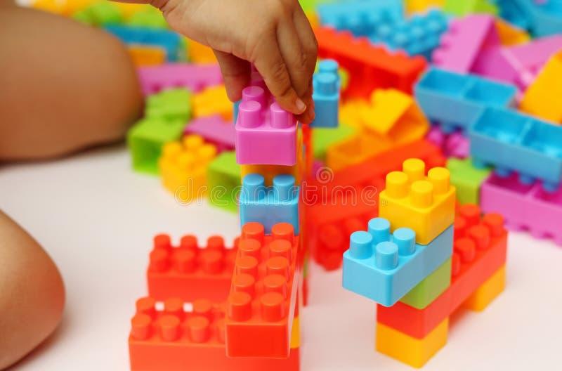 Bloques plásticos del juguete del edificio de la mano del ` s del niño con el fondo borroso foto de archivo libre de regalías