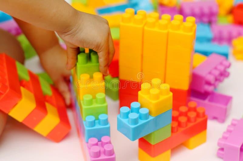 Bloques plásticos del juguete del edificio de la mano del ` s del niño con el fondo borroso imagen de archivo