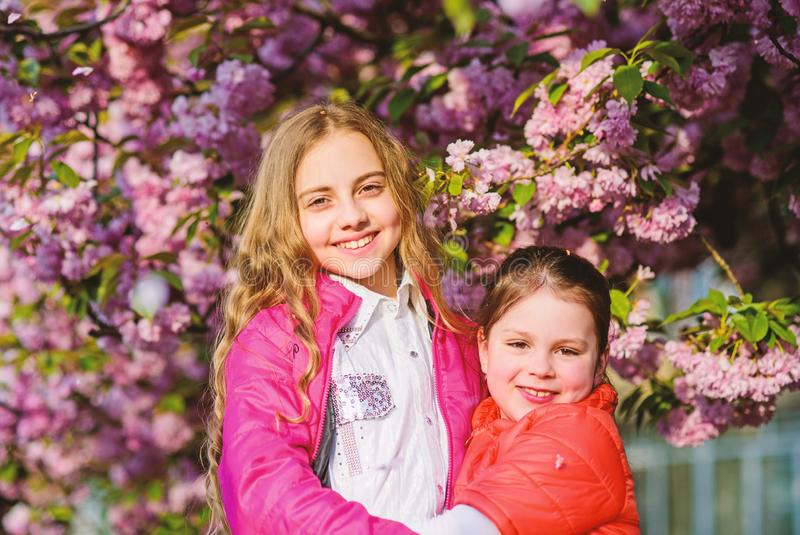 Blossom smell, allergy. Sisterhood. Natural cosmetics for skin. happy sisters in cherry flower. Sakura blooming. summer. Childhood beauty. Family day. small royalty free stock image