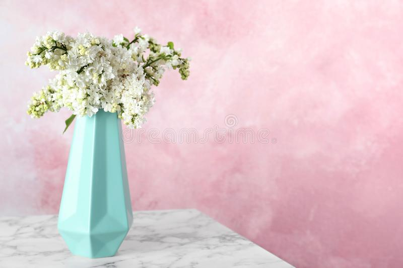 Blossoming lilac flowers in vase on marble table against color background royalty free stock images
