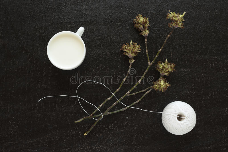 Blossoming twig, milk and a cotton skein royalty free stock photography