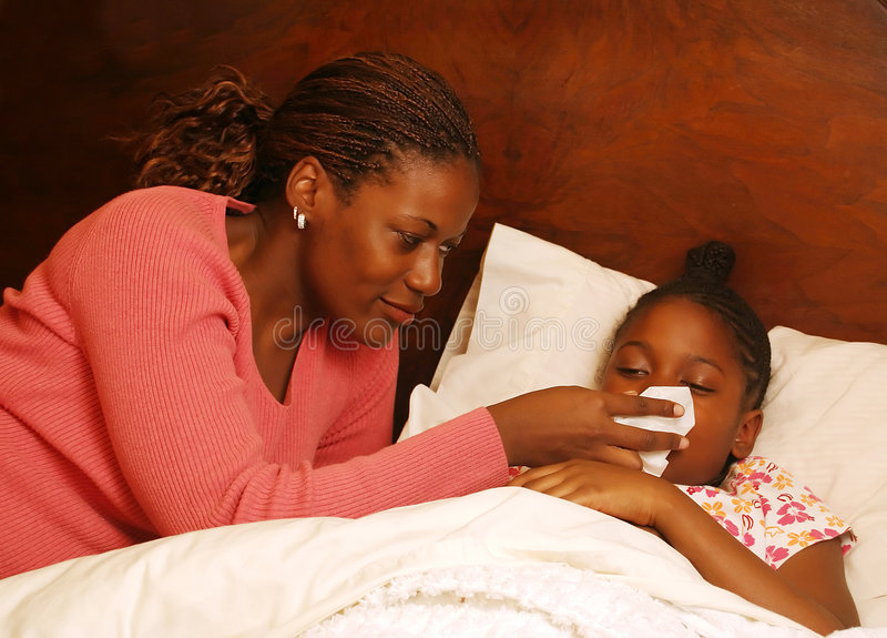 Blow. A mother helps her sick daughter blow her nose royalty free stock image