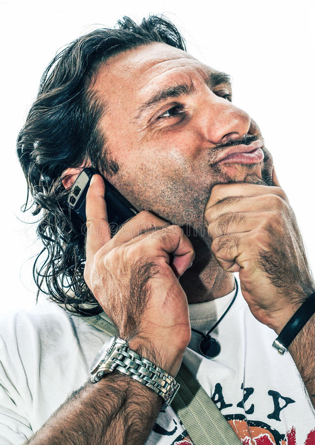Blowhard hairy. Man overly confident. An Italian man with beard and many hairs are on the phone. His attitude is strange, he poses with curious expression. On stock photography