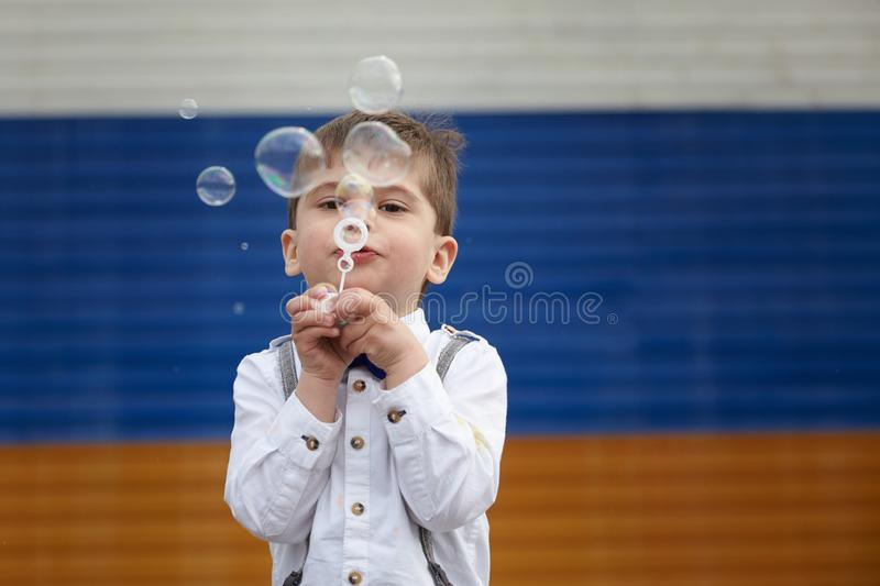 Blowing bubbles. a child plays in soap bubbles royalty free stock photo