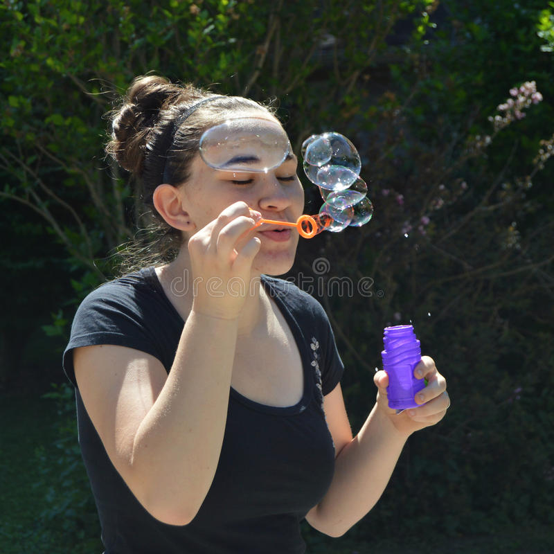 Blowing Bubbles. A teen girl blowing bubbles with an orange wand and a purple bottle. She is wearing a black shirt and has her hair in a bun royalty free stock images