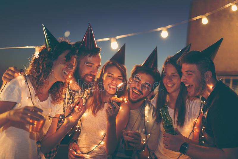 Blowing the candle on a birthday cake. Group of young friends having a birthday party at a building rooftop, singing a song and blowing a candle. Focus on the stock photo
