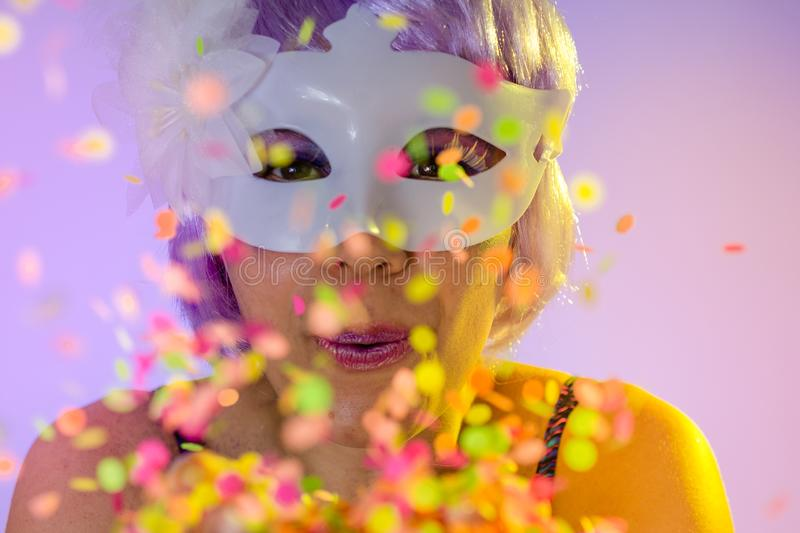 Blowing Confetti. Portrait of latin woman wearing purple wig and makeup mask. Colorful background. Carnival concept, fun and party. Carnaval Brazil. Blowing stock photography