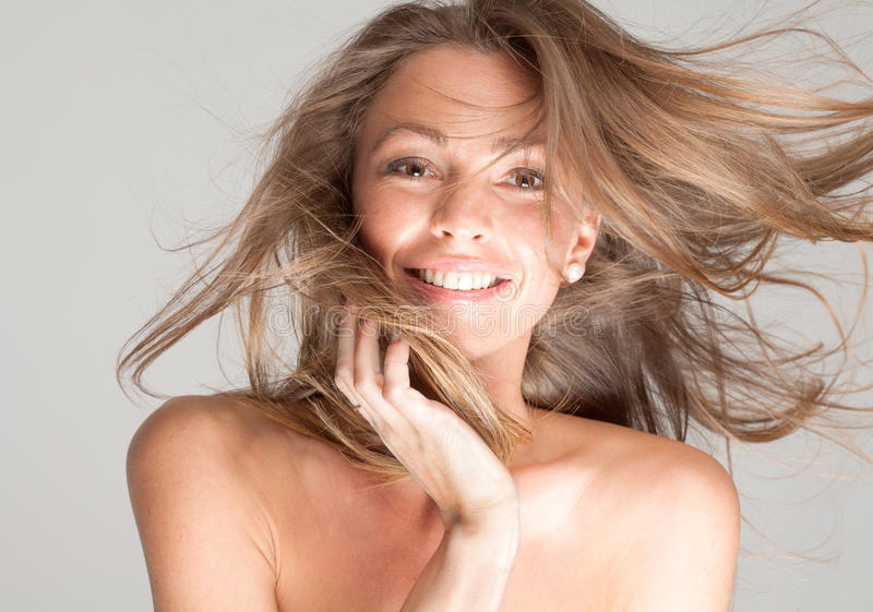 Blowing Hair and Big Smile. A portrait of a gorgeous woman with wildly blowing hair and a happy smile royalty free stock photo