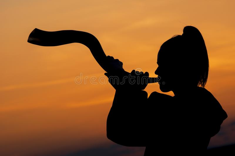 Blowing Horn Sunset. A woman is blowing a horn at sunset royalty free stock images
