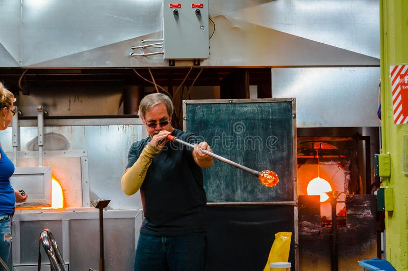 Blowing molten glass into a dish royalty free stock photography