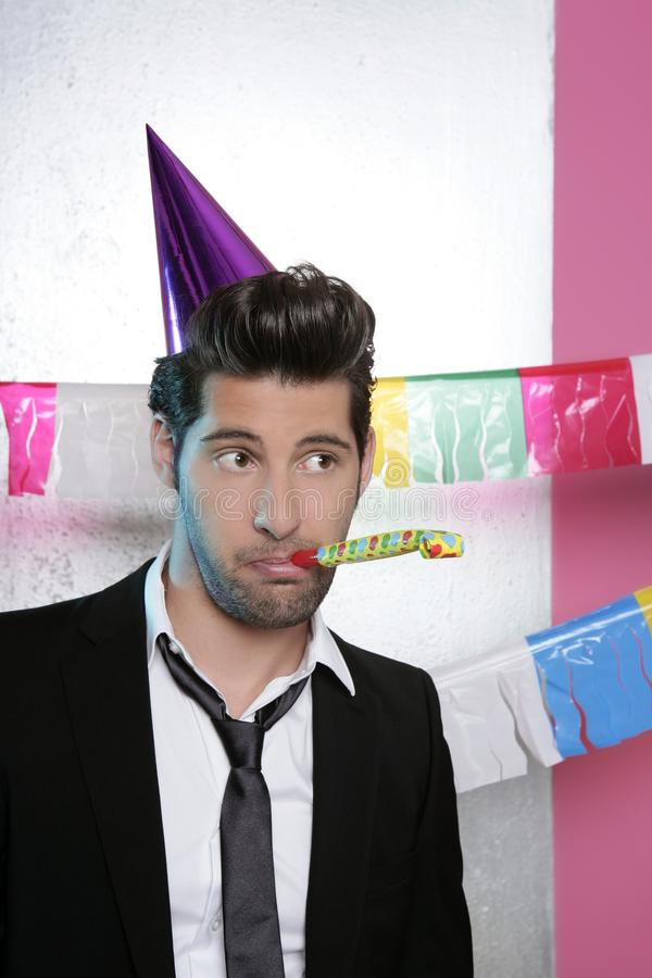 Blowing noisemaker suit party funny young man stock photo
