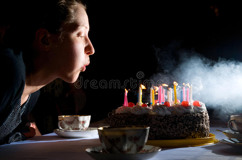 Blowing out candles on cake. Young woman is blowing out candles on cake stock photography
