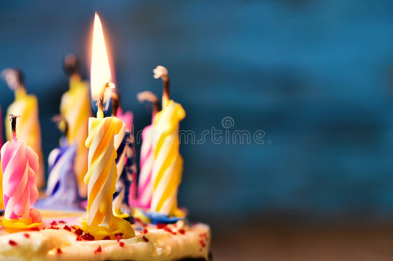 Blowing out the candles of a cake. Closeup of some unlit candles and just one lit candle after blowing out the cake royalty free stock photos