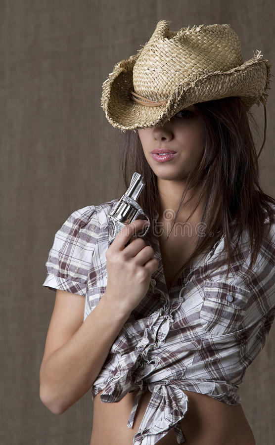 Blowing the smoke out. Young brunette cowgirl blowing on a small gun stock photos