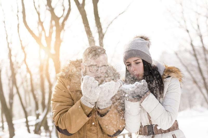 Blowing the snow away. Young couple in love having fun on a snowy winter day, blowing snow away stock photos