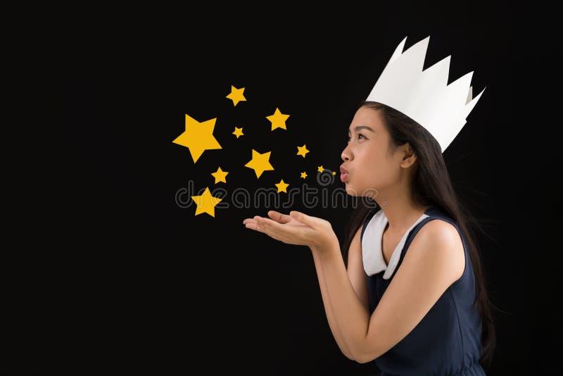 Blowing stardust. Vietnamese teenage girl in paper crown blowing stardust stock photography