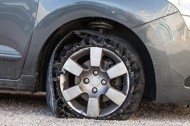 Blown out tire with exploded, shredded and damaged rubber. Destroyed blown out tire with exploded, shredded and damaged rubber on a modern suv automobile. Flat stock images