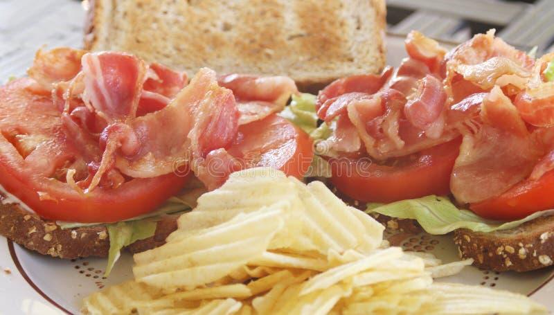 BLT aprono il panino del fronte su grano con i chip fotografia stock