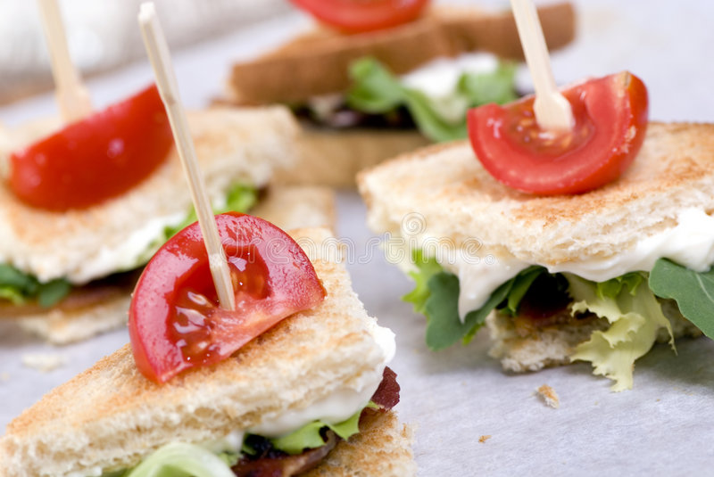 BLT wedges. A gourmet BLT sandwich cut into wedges with a small tomato on top royalty free stock image