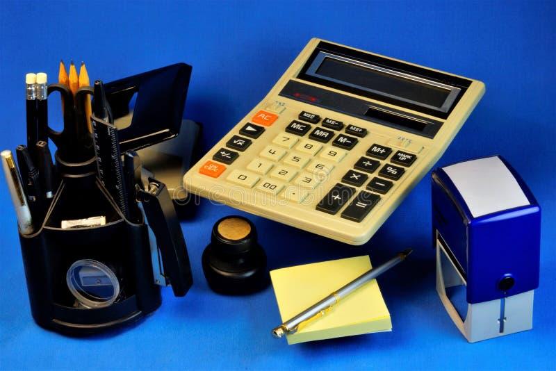Blu del fondo della scrivania di contabilità, con gli accessori necessari per il lavoro fotografia stock