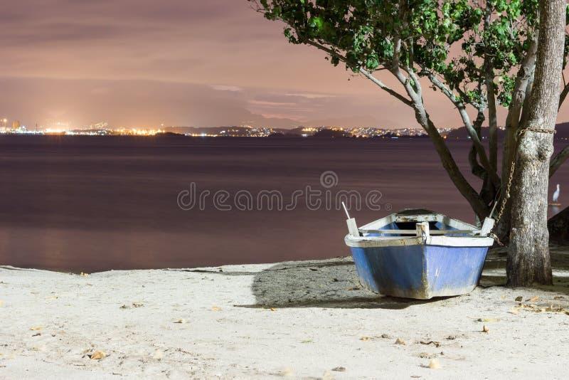 Blu e bianco wodden la barca del pescatore incatenata ad un albero alla spiaggia Isola di Paqueta, Brasile fotografia stock libera da diritti
