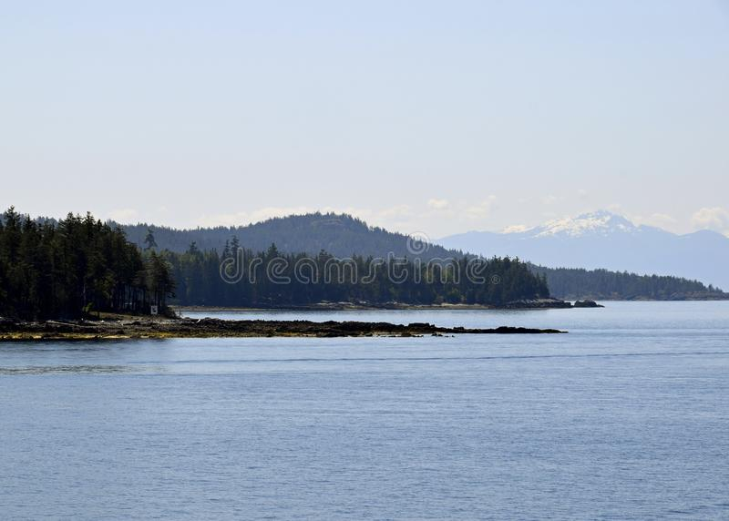 Blubber Bay and Vancouver Island Mountain ranges. Scenic seascape along the shoreline of the Texada Island near Blubber Bay, Vancouver Island Mountain ranges in stock photos