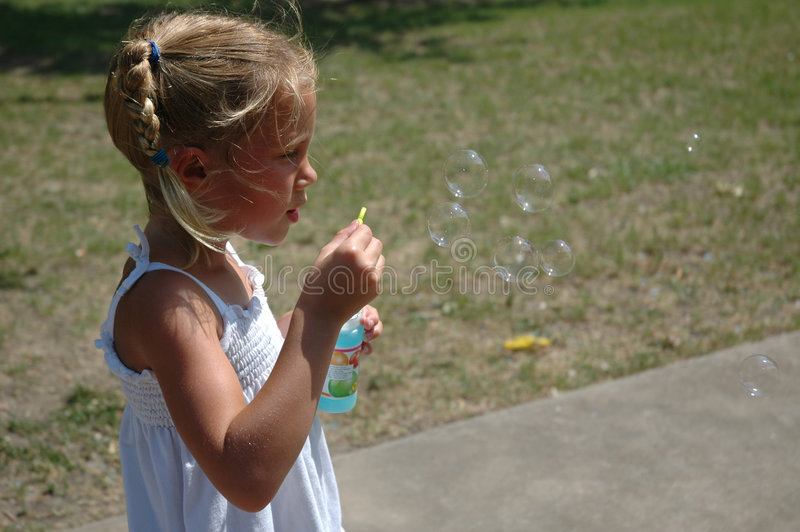Blubble Blower. Young girl blowing bubbles. Beautiful Young blonde model royalty free stock photography