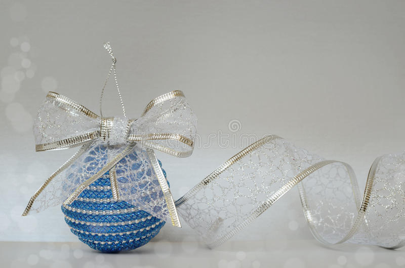 Blue Ð¡hristmas ball and glitter ribbon. On a silver background stock photo