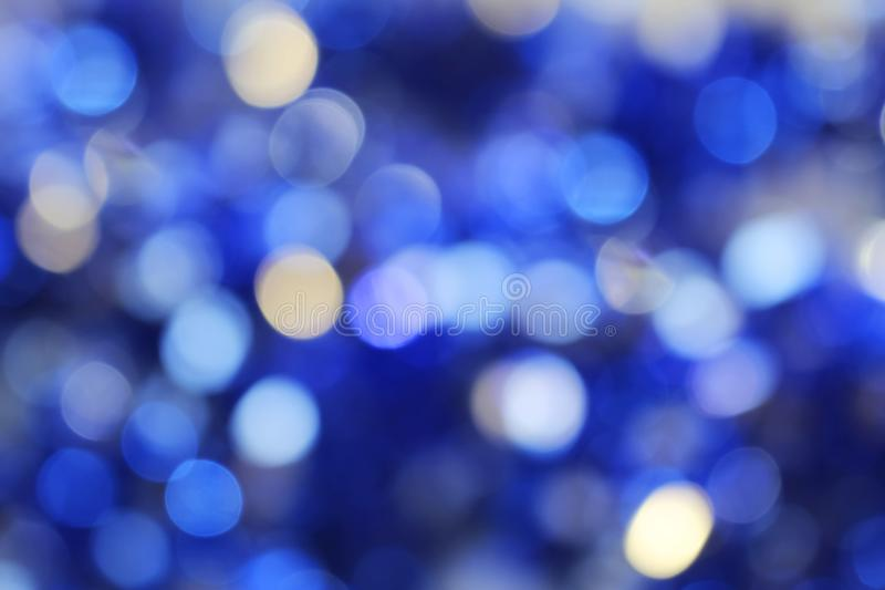 Blue abstract bokeh lights defocused background. Bright glowing blue abstract bokeh lights defocused background royalty free stock images