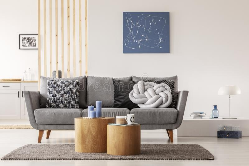 Blue abstract painting on white wall of contemporary living room interior with grey settee with pillows. Real photo stock photo