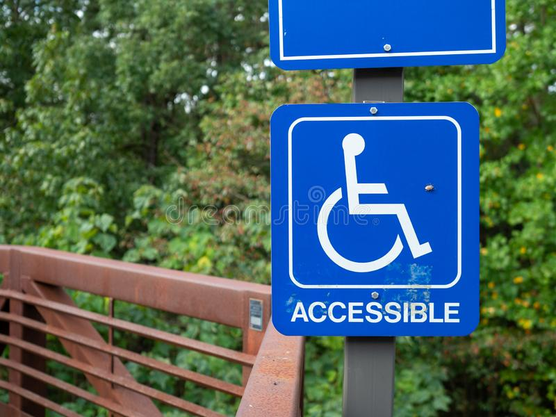 Blue accessible handicap sign hanging on nature hiking path stock photo