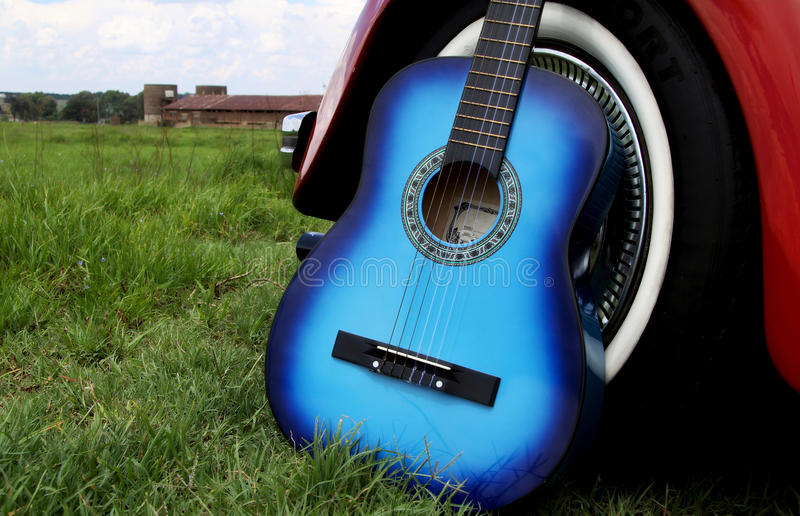 Blue acoustic guitar. Artistic processing of blue acoustic guitar against a red old VW beetle stock images