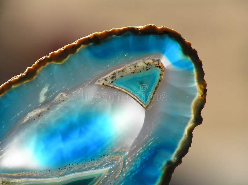 Blue agate. Close-up of slice of blue agate against blurred background stock image