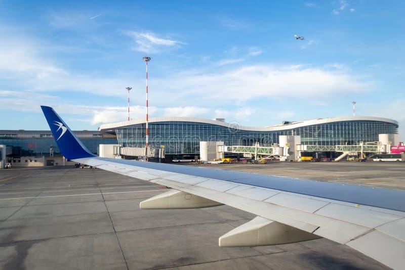 Blue Air-vliegtuig ter plaatse in Henri Coanda International Airport, die voor vertrek voorbereidingen treffen stock afbeelding
