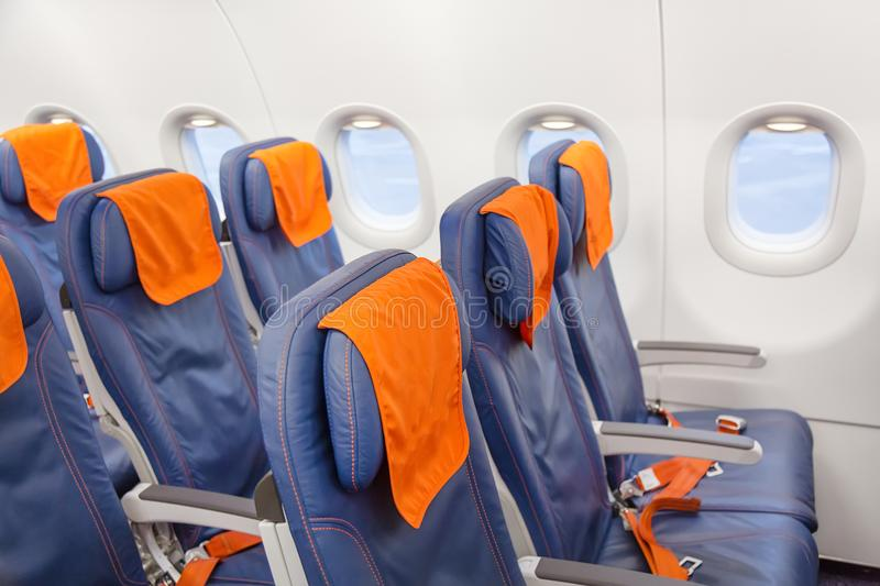 Blue airplane empty seats with windows. Aircraft interior. royalty free stock photo