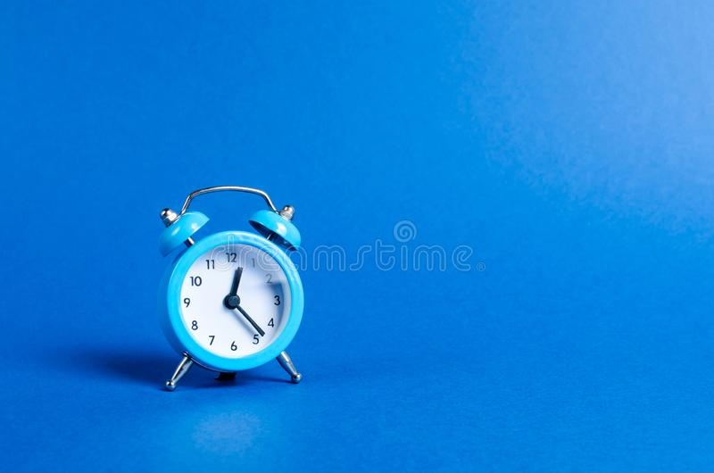 A blue alarm clock on a blue background. Limited offer and over time. Planning and discipline. waiting for a meeting. Punctuality royalty free stock images