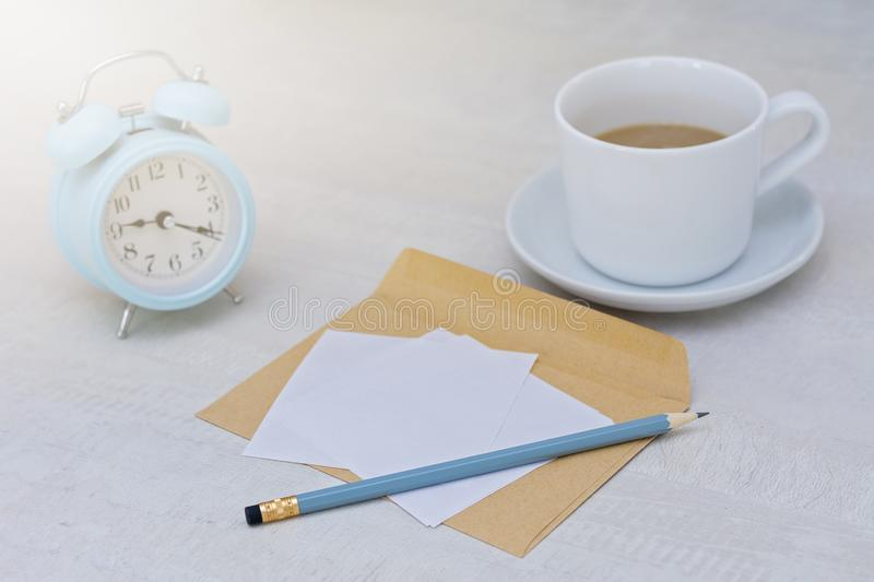 Blue alarm clock in morning light, cup of coffee and letter on table royalty free stock photo