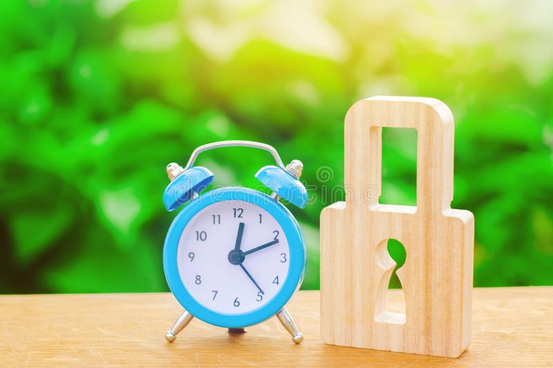 Blue alarm clock and padlock. Non-durable protection time-tested protection and stability. Saving time. The concept of a temporary stock images