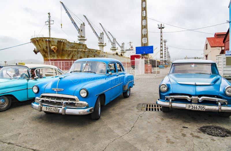 Blue american classic cars and rusty ship, Santiago de Cuba stock image